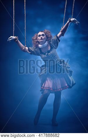 Theater of life. The actress plays a doll on strings at a performance in a puppet theater. Full length portrait in retro style.