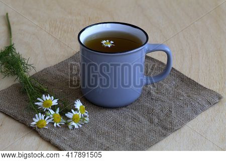 Cup Of Tea With Flowers.hot Drinks. Grey Mug Of Chamomile Tea On Sackcloth. Cup Of Hot Herbal Chamom