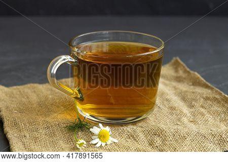 Hot Drinks. Mug Of Chamomile Tea On Sackcloth. Glass Cup Of Iced Herbal Chamomile Tea On A Black Tab