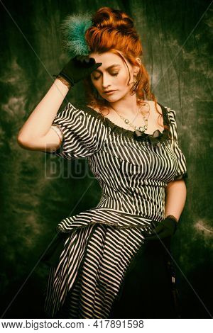 Fashion history, makeup and hairstyle. Portrait of a beautiful red-haired woman in a 19th century dress on a vintage background. Victorian style.