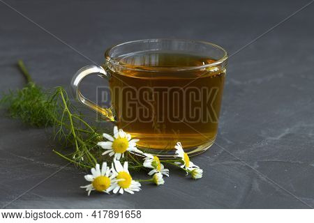 Mug Of Chamomile Tea. Glass Cup Of Iced Herbal Chamomile Tea On A Black Table With Copy Space. Cup O