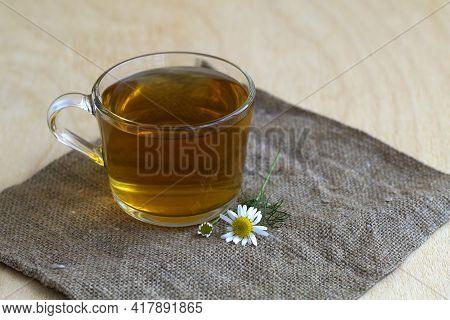 Cup Of Tea.hot Drinks. Mug Of Chamomile Tea On Sackcloth. Glass Cup Of Hot Herbal Chamomile Tea On A