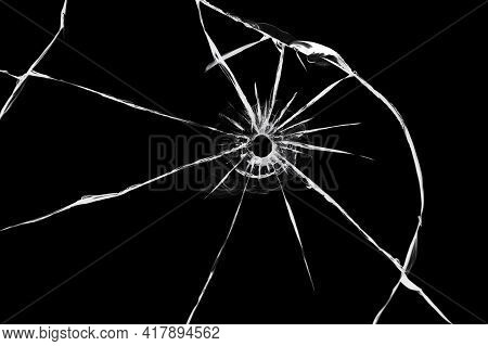 The Effect Of Cracks On Broken Glass From A Shot Of A Weapon. A Hole In The Glass Of The Bullet.