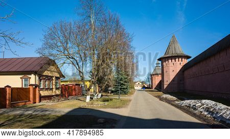 Street of Suzdal, Red Wall and towers of Saint Euthymius monastery, residential russian traditional house across road in sunny day in spring middle april, Golden Ring of Russia