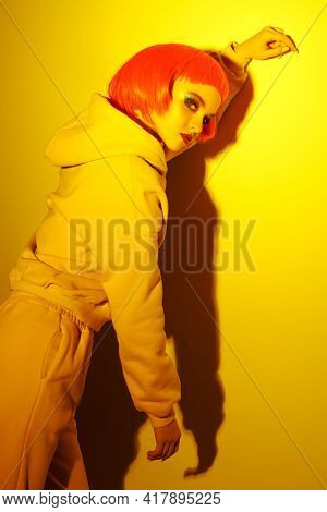 Sensual contemporary girl with bright makeup and short pink wig poses in tracksuit in yellow light. Sport chic fashion. Youth fashion and beauty trends.