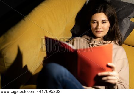 Attractive Long-haired Girl Intently Reads Book On Comfy Sofa Under Spot Lamp