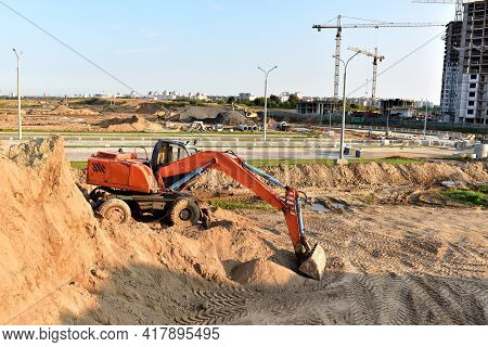 Excavator Working At Construction Site On Earthworks. Backhoe On Road Work And Aying Sewer Pipes. Co
