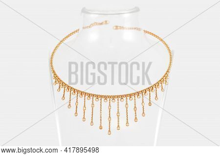 Golden Necklace With Diamonds On Transparent Jewelry Neck Stand In Boutique. Yellow Gold With Diamon