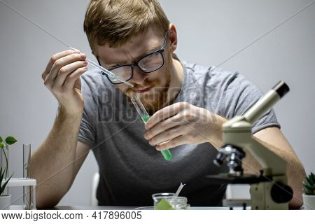 Bearded Biologist In Glasses Conducts Chemical Experiment With Green Reagent