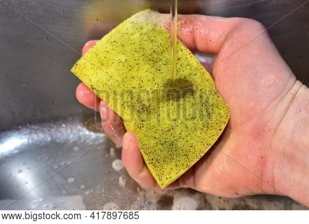 Sponge In Hand With Detergent And Foam While Washing Sink In The Kitchen. Wash Dishes And Plumbing.