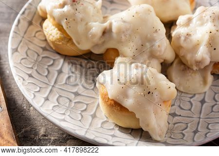 Traditional American Biscuits And Gravy For Breakfast On Wooden Table. Close Up