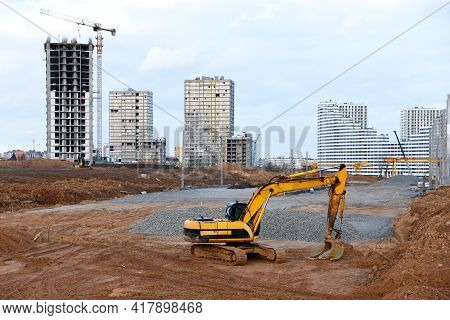 Excavator On Earthworks At Construction Site. Backhoe On Road Construction. Tower Cranes In Action O