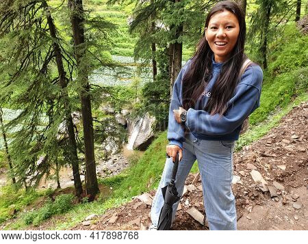 Photo Of A Beautiful South Asian Young Woman Smiling With Looking At Camera While Hiking In Hilly Ar