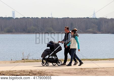 Moscow, Russia - April 2021: Happy Couple With Baby Pram Walking On River Background In Spring City.