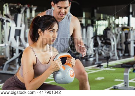 Portrait Of Asian Women In Sportswear Doing Squats Workout In Fitness Gym With Her Handsome Muscular