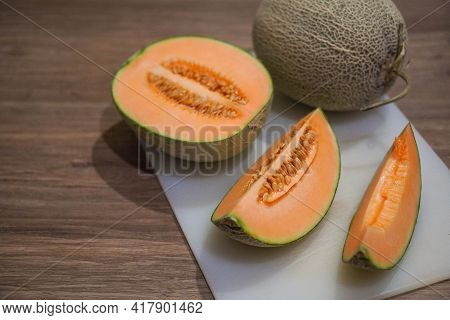 Orange Cantaloupe Cut Put It On A White Plastic Chopping Board On A Wooden Floor