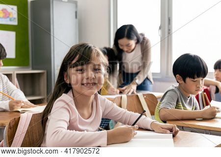 Portrait Of Asian Elementary School Kids Studying In A Classroom. The Girl Smiled And Looked At The