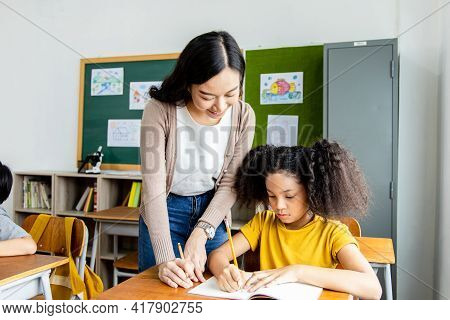 An Asian Woman Teacher Teaches An African American Child Student A Lesson In The Classroom. They Smi