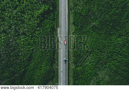 Aerial View Of Toll Road Highway With Cars And Trucks Through Green Forest