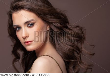 Portrait Of Pretty Young Woman With Blowing Healthy Curly Hairdo And Clear Skin On Brown Background