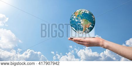 Hands Holding A Planet, Earth On A Background Of Nature Blue Sky With Beautiful White Clouds And Sun
