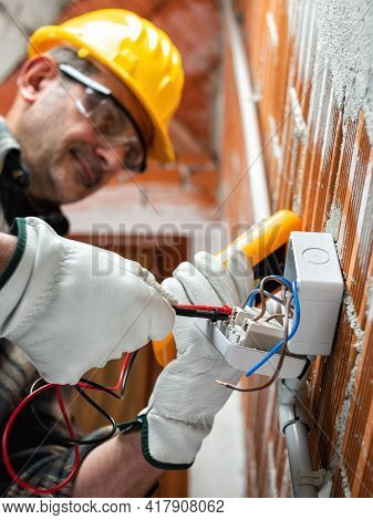 Electrician At Work In An Electrical System Of A Construction Site. Construction Industry.