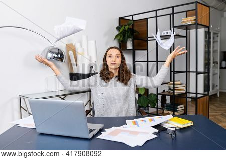 Irritated Business Woman Has Messy On The Desk, A Female Employee Looking Through Workpapers On The