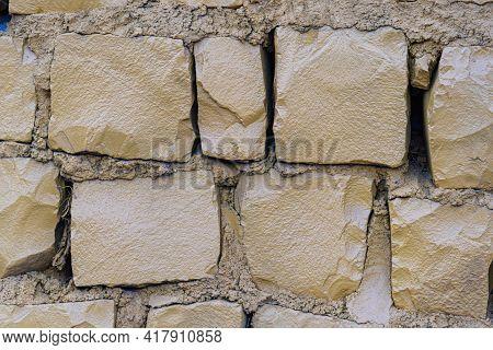 Urban Retaining Wall Built With Basalt Stones. Rock Wall Of Basaltic Rock. Basaltic Stones With Grou