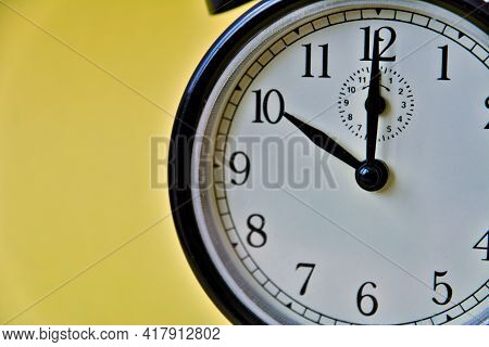 Shot Of Vintage Retro Analog Clock On Yellow Background Showing 10 O Clock