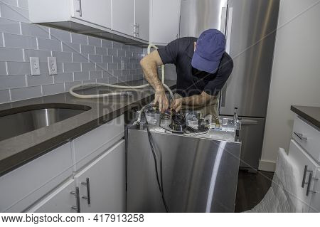 Appliance Repairman Working On A Dishwasher Installing The Water Hoses