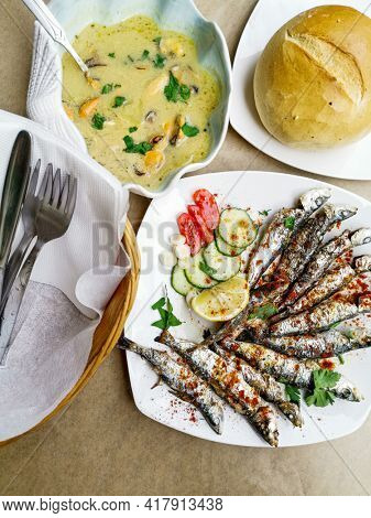 Fresh Grilled sardines served with fresh tomatoes, cucumbers slices and lemon on white plate for mediterranean healthy meal