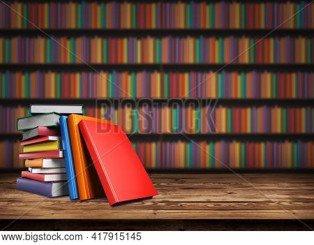 Wooden Table With A Stack Of Colored Book. Blurred Background From Book Shelves. Table Top With Book