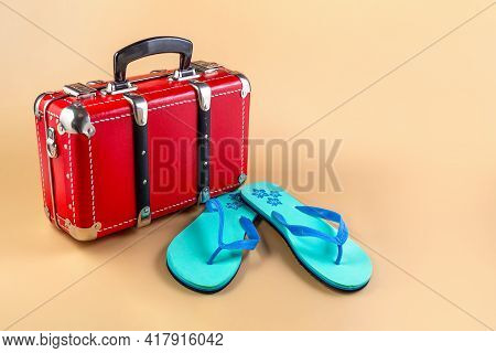Red Suitcase And Beach Slippers, Slates. Travel Suitcase For Travel. Concept. Place For Your Text.