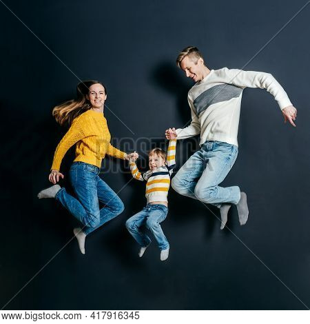 Happy Smiling Family Jump On Black Background..