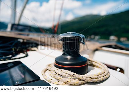 Black Halyard Winch With A Variegated Cable Against The Backdrop Of A Mountain Landscape