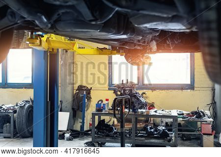 Bottom Pov Big Modern Suv Car With Removed Gearbox Raised On Lift Elevator At Workshop Service Maint