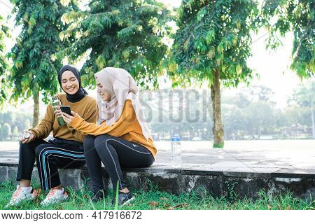 Two Girls In Veil Sits With Chatting When Exercise Breaks While Using Handphone And Drink Water With