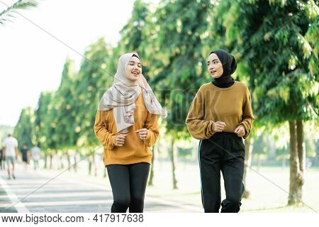 Two Beautiful Girls In Veil Do Outdoor Sports While Jogging Together