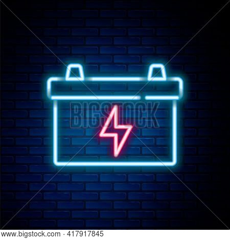 Glowing Neon Line Car Battery Icon Isolated On Brick Wall Background. Accumulator Battery Energy Pow