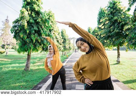 Two Girls In Veil Do Arm Stretches By Raising Their Arms Upward With Their Bodies Leaning To The Sid