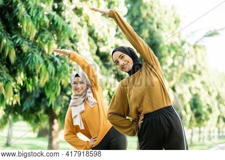Two Asian Girls In Veil Do Arm Stretches By Raising Their Arms Upward With Their Bodies Leaning To T
