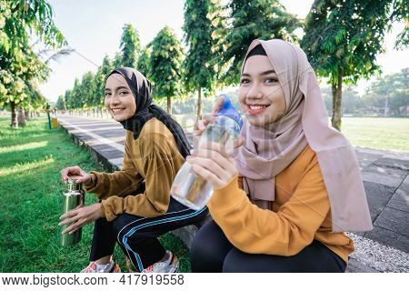 Smiling Two Muslim Teenage Girls Drinking Water Using Bottles After Sports Together In The Afternoon