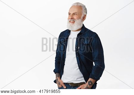 Handsome Senior Man With Tattoos Standing Half-turned, Looking At Promotional Text And Smiling Pleas