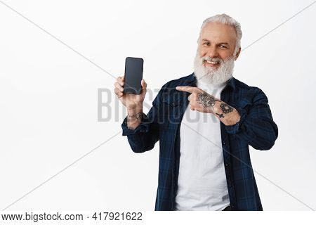 Happy Senior Man Pointing At Mobile Phone Screen With Tattoed Hand, Laughing And Smiling Cheerful, S