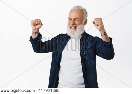 Relieved And Excited Old Man Winning Prize, Raising Fists Up And Say Yes, Smiling Satisfied, Achieve