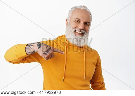 Happy Handsome Senior Man With Tattoos Point At Himself, Smiling Pleased, Talking About Him, Self-pr