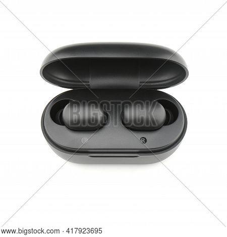 In-ear headphones. Black wireless earphones in-ear with charging case. Wireless earbuds or earphones