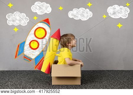 Happy Child With Toy Paper Rocket Wants To Fly. Funny Kid Dreams About Space. Imagination, Freedom A