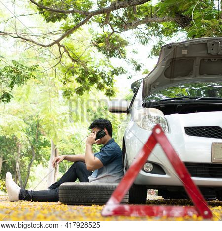 Asian Man Sitting Beside Car And Using Mobile Phone Calling For Assistance After A Car Breakdown On