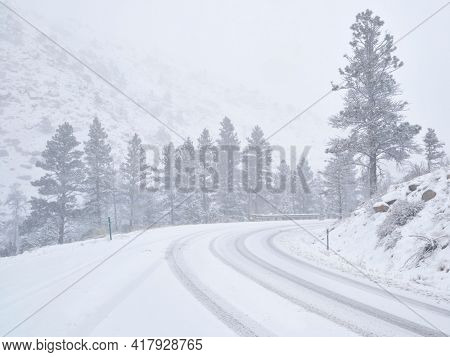 winter travel in Colorado Rocky Mountains - highway 14 in Poudre Canyon in a heavy early spring snowstorm